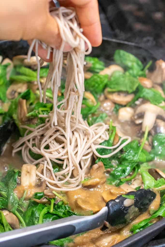 noodles being added to a pan with cooked spinach, mushrooms, and miso sauce.