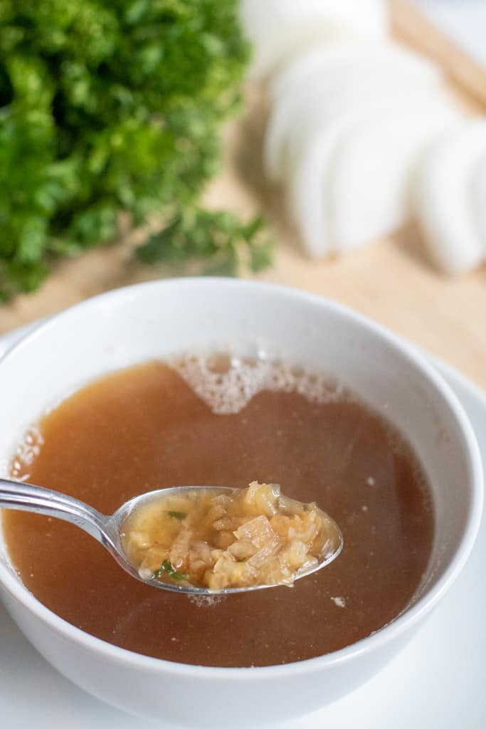 a small bowl of onion soup with a spoon scooping out some onions.