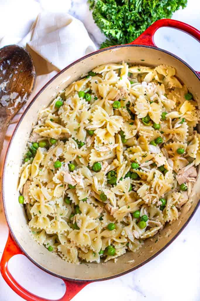 overhead of a pot of pasta with peas and tuna.