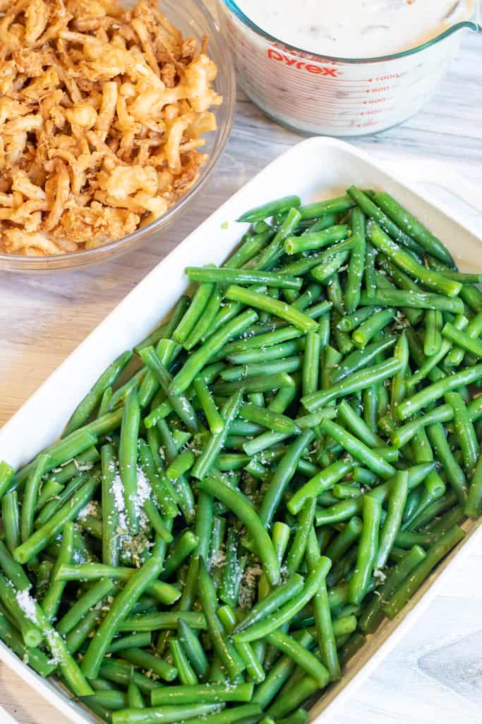 fresh green beans in a dish next to mushroom soup and fried onions.