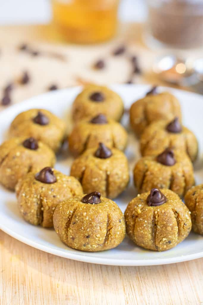 a plate of pumpkin shaped bliss balls topped with chocolate chips.
