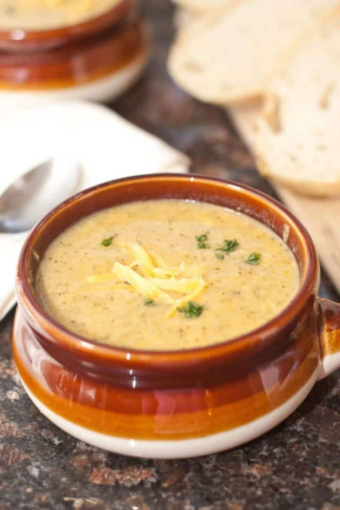 a soup crock with creamy broccoli cheddar soup with shredded cheese on top.